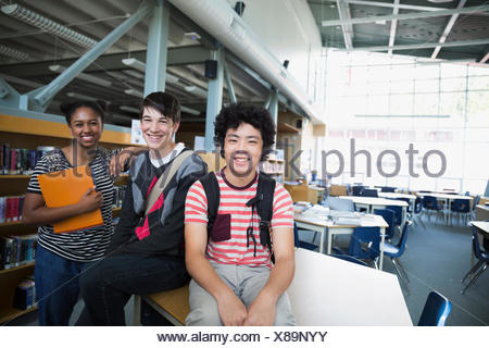 Portrait confident high school students in library - Stock Photo
