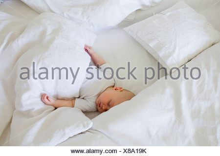 Baby girl asleep in bed - Stock Photo