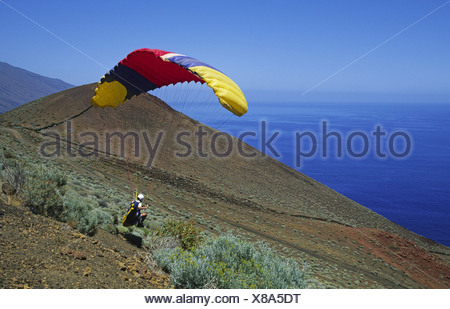 Man with a hang glider on the South coast ready to go, Canary, El Hierro - Stock Photo