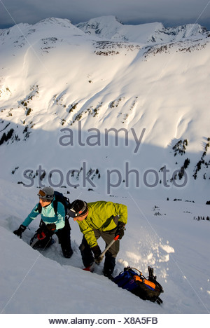 Male and female skiers testing snow slope for avalanche safety, MacGillivray Pass, Coast Mountains, British Columbia, Canada. - Stock Photo