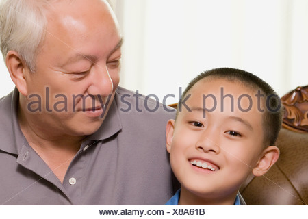 Close-up of a boy smiling with his grandfather - Stock Photo