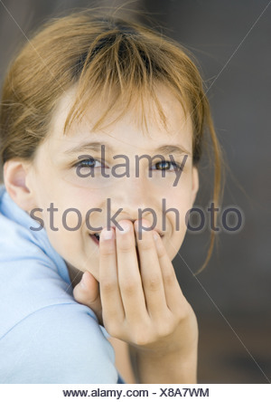 Girl covering mouth looking at camera, smiling, portrait, close-up - Stock Photo