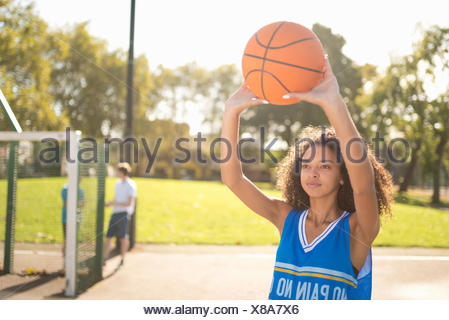 Young female basketball player holding up basketball - Stock Photo