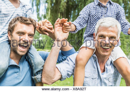 Mid adult man with father giving sons shoulder carry race in garden - Stock Photo
