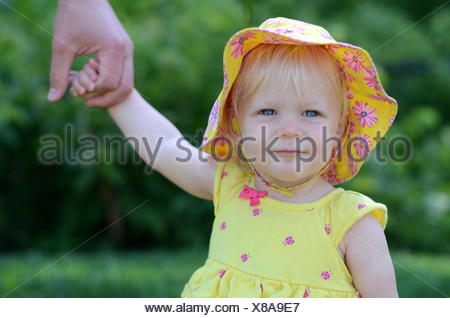 Baby girl holding her father's hand - Stock Photo