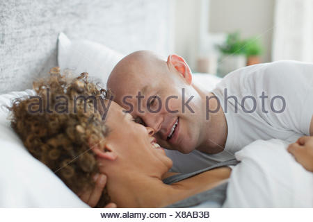 Couple being affectionate in bed together. - Stock Photo
