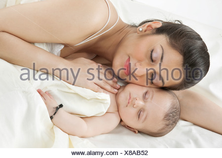 Mother sleeping with her baby - Stock Photo
