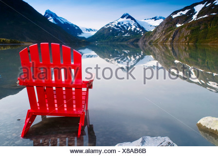 Red Adirondack chair at Portage Lake with Chugach Mountains in the background, Southcentral, Alaska - Stock Photo