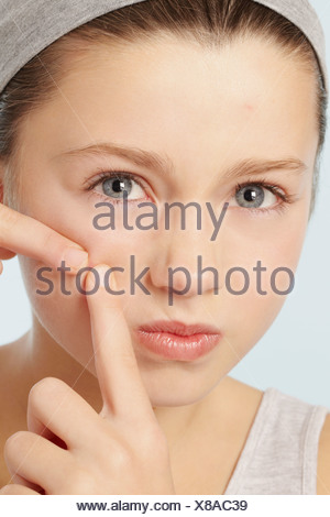 Girl squeezing spot on her face - Stock Photo