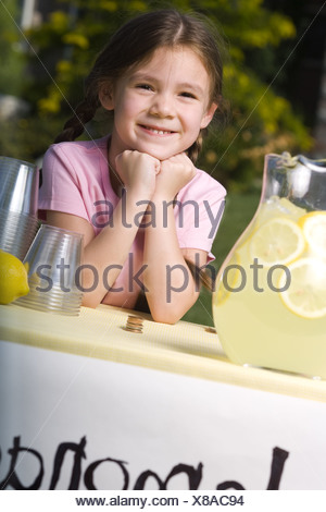 Portrait of a girl leaning on a table and smiling - Stock Photo