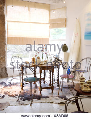 Metal chairs at Jacobean style table in coastal dining room with rough linen blinds on the windows - Stock Photo
