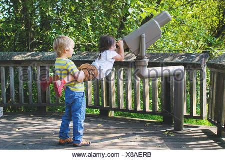 Boy lifting girl to look through telescope - Stock Photo