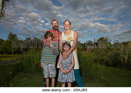 Portrait of couple with children on family herb farm - Stock Photo