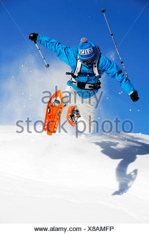 man with snow shoes jumping over a snow-covered slope, France - Stock Photo