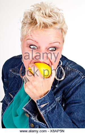 portrait of middelaged beautiful woman eating fresh lemon - Stock Photo