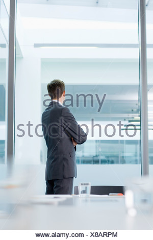 Pensive businessman looking out window in conference room - Stock Photo