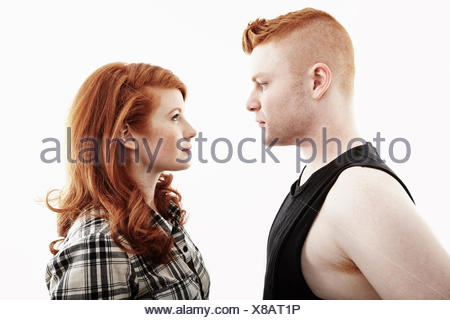 Studio portrait of red haired young couple gazing face to face - Stock Photo