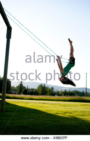 A young women swinging smiles while looking back on a summer evening in Idaho. - Stock Photo