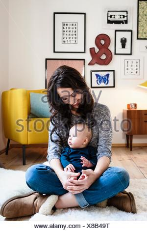Mother and baby son sitting in living room - Stock Photo
