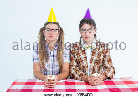 Unsmiling geeky hipsters celebrating birthday - Stock Photo