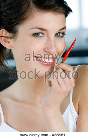 Young smiling woman holding red chili pepper - Stock Photo