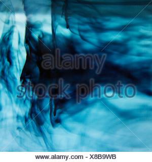 Blue ink swirling in liquid - Stock Photo