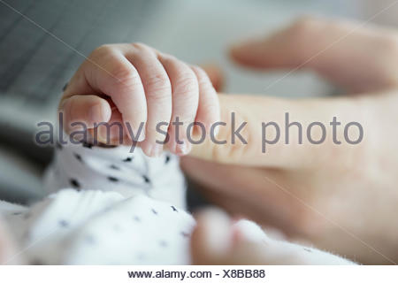 Close-up of baby holding father's finger - Stock Photo