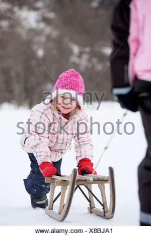 Young girl towed on sledge - Stock Photo
