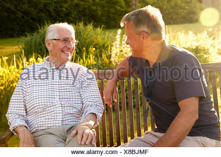 Man Visiting Senior Male Relative In Assisted Living Facility - Stock Photo