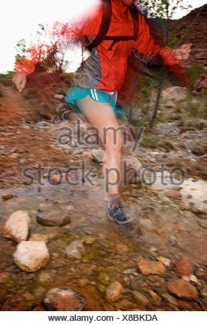 A woman trail running through a rocky stream in Nevada.