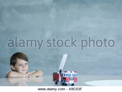 Boy looking at toy firetruck - Stock Photo