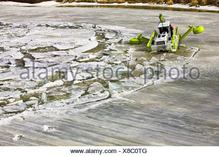 An Amphibex machine breaking up ice on the Red River, Selkirk, Manitoba, Canada - Stock Photo