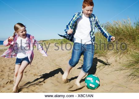 Girl and boy chasing football across sand, smiling - Stock Photo