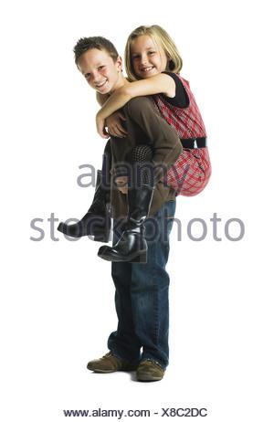 Boy giving girl piggy back ride smiling - Stock Photo