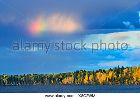 Rainbow over Waskasiu Lake Prince Albert National Park Saskatchewan Canada - Stock Photo