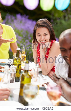 Young Woman Relaxing At Outdoor Barbeque - Stock Photo
