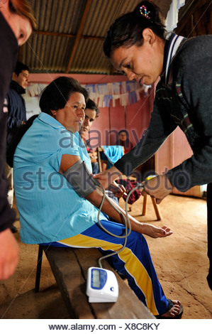 The blood pressure of a woman is being measured, by an aid organisation examining and advising mothers about health issues - Stock Photo