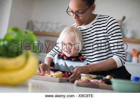 Mother helping sone prepare food in kitchen - Stock Photo