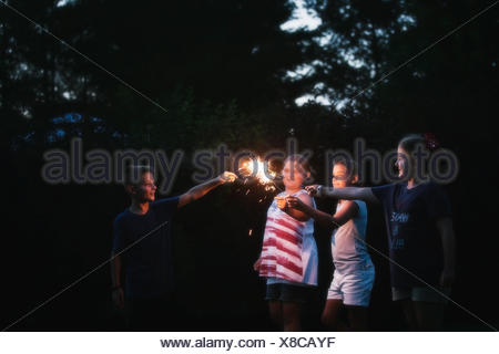 Boy and three girls igniting sparklers together at night on independence day, USA - Stock Photo