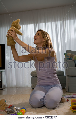 Young mother and teddy bear - Stock Photo