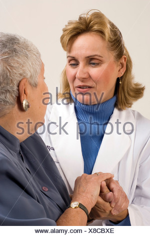 A compassionate healthcare professional listens to her patient. - Stock Photo