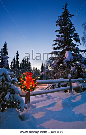 Decorated Christmas wreath hangs on a snowcovered split rail fence at dusk, Alaska - Stock Photo