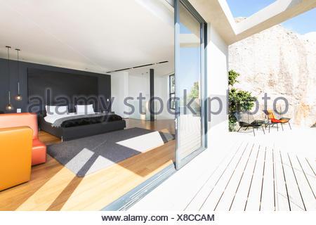 Sliding glass door onto bedroom in modern house - Stock Photo