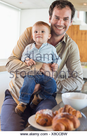 Man with his son smiling at a kitchen counter - Stock Photo