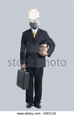 Businessman with a light bulb on his head - Stock Photo