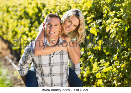 Portrait of smiling man giving his woman a piggyback next to grapevine - Stock Photo
