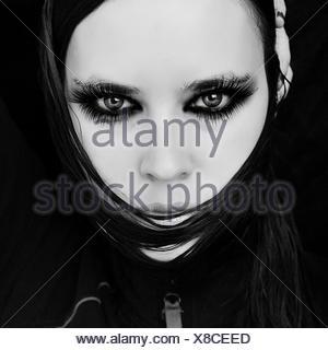 Close-Up Portrait Of Confident Beautiful Woman Against Black Background