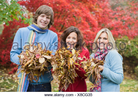 three people outdoors at a park holding leaves - Stock Photo