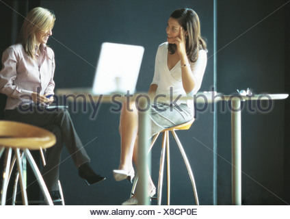 Businesswomen sitting and talking in cafe setting - Stock Photo