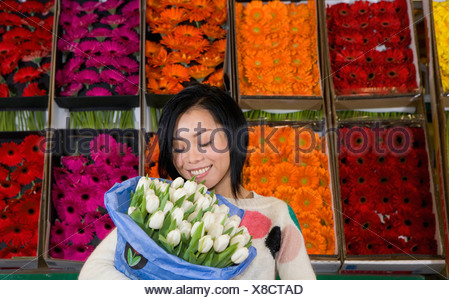 Woman holding bunch of flowers - Stock Photo